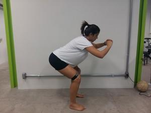 [FOTO] Agachamento Isométrico 45° - Foco em extensores de quadril e joelho – Glúeo máximo e isquiotibiais. Em pé, com uma faixa elástica ao redor dos joelhos, inclinar o tronco para frente, agachar até 45º sem levar os joelhos para frente em direção aos pés. Repetir 3 séries x 15 repetições.